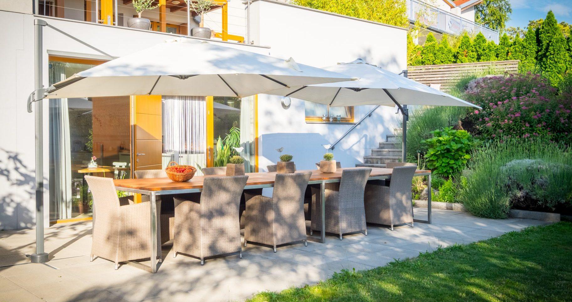 Gartenansicht SCHEIBER Gästehaus mit Tisch und Sonnenschirmen