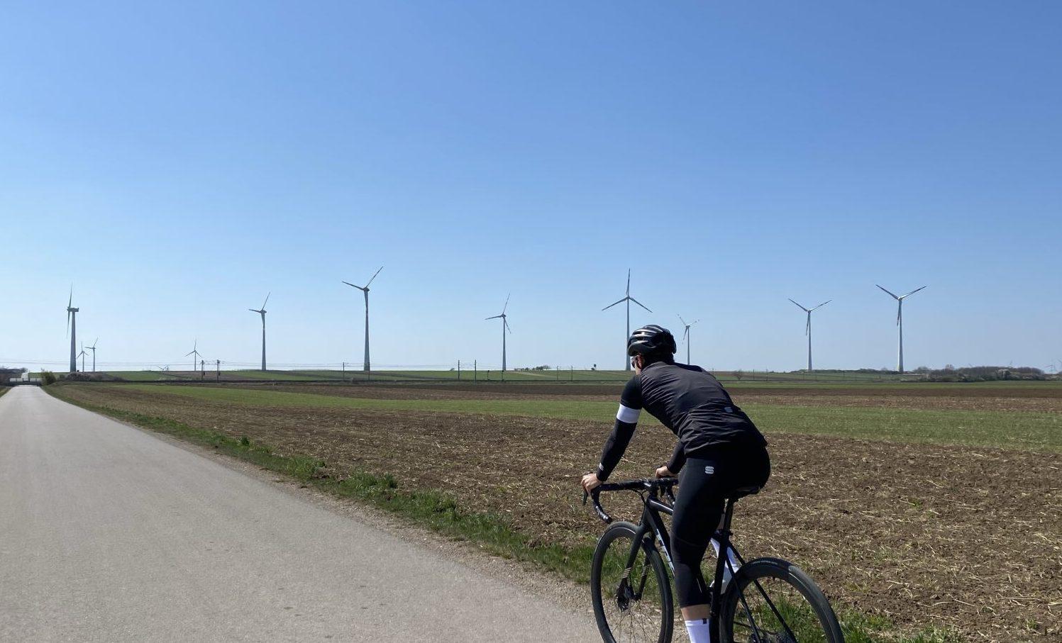 Radrennfahrerin auf gerader Straße mit Windrädern im Hintergrund.