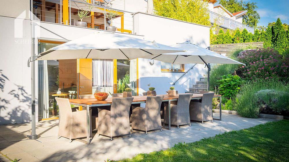 Gartenasicht des Gästehauses mit Tisch und Sonnenschirmen